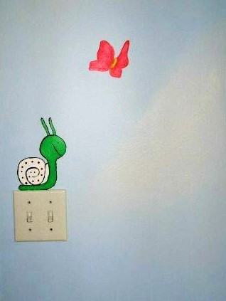 A butterfly mural has fun accents like fluffy clouds and a snail, painted by Adrienne of AboutMurals.ca