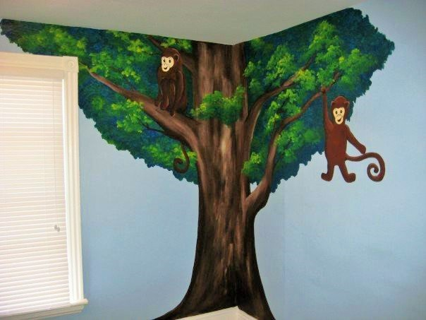 A jungle mural featuring monkeys swinging from a tree, painted by Adrienne of AboutMurals.ca