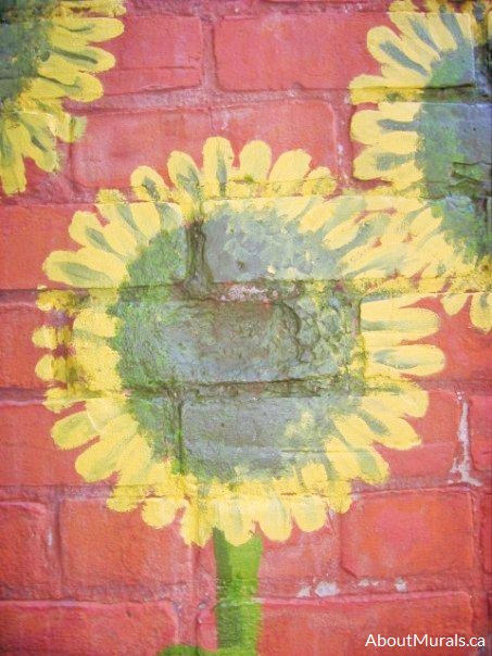 A closeup photo of a sunflower mural painted by Adrienne of AboutMurals.ca