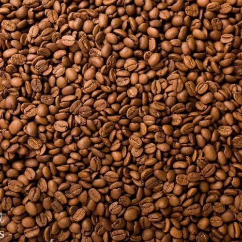 A closeup photo of brown coffee beans printed on removable wallpaper from AboutMurals.ca