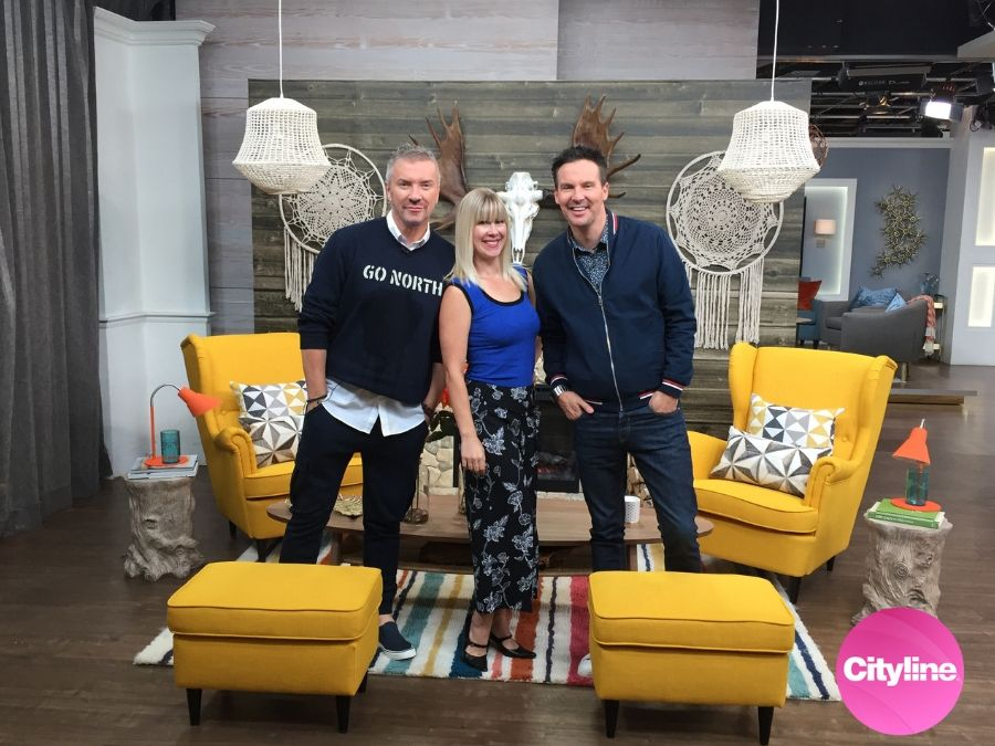 Adrienne stands with Colin and Justin on set at Cityline with her horizontal barn wood wall mural in the background