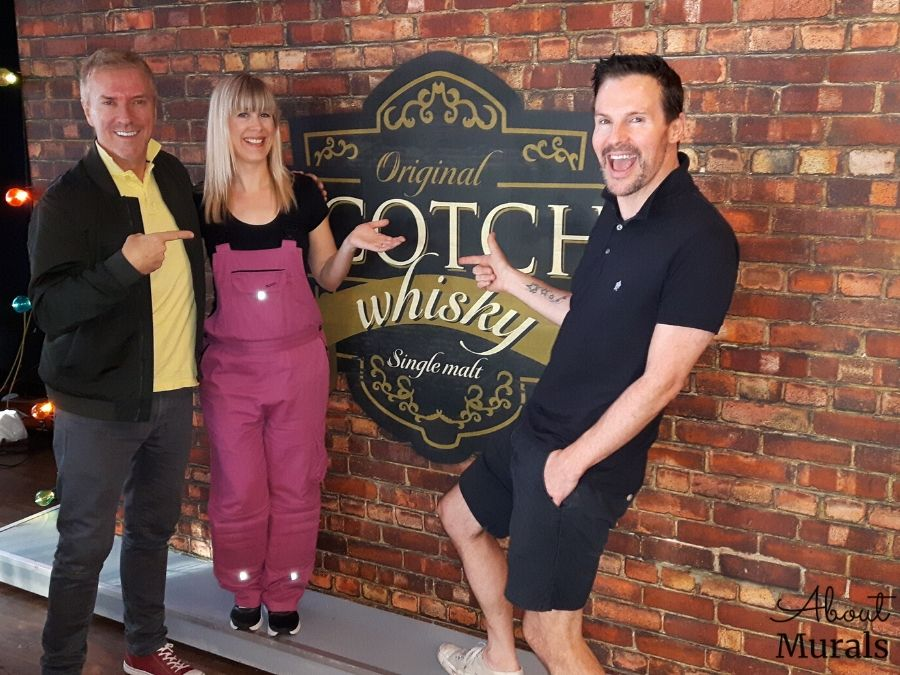 A brick look wallpaper is the backdrop on Cityline with Colin and Justin and Adrienne of AboutMurals.ca