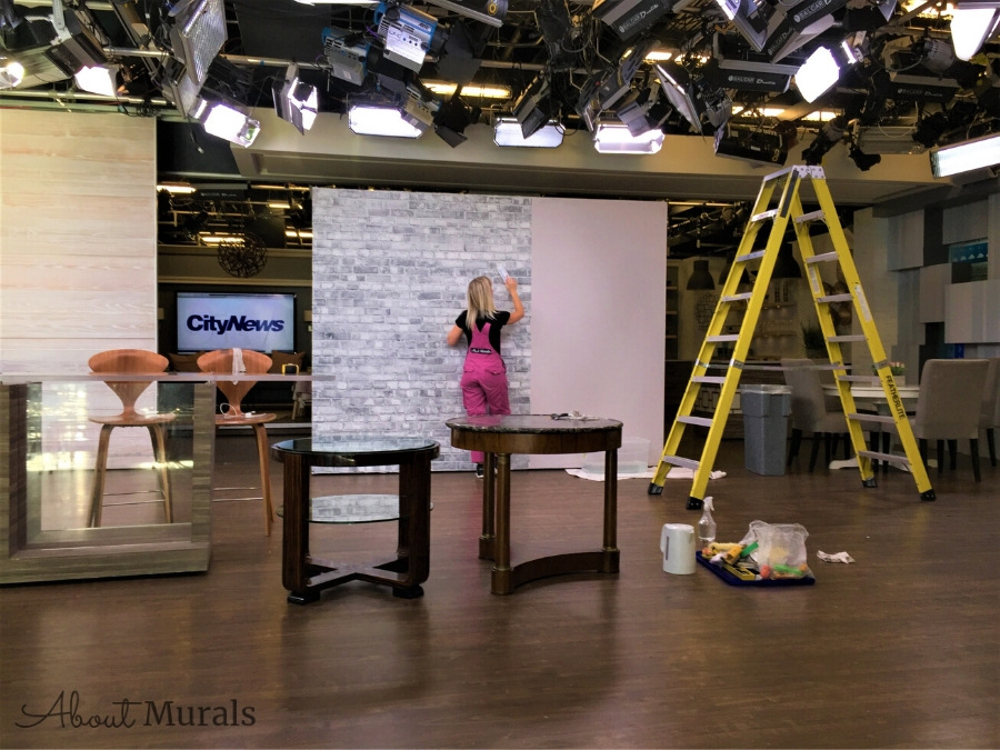 Adrienne from AboutMurals.ca installs a grey brick wallpaper on set at Cityline