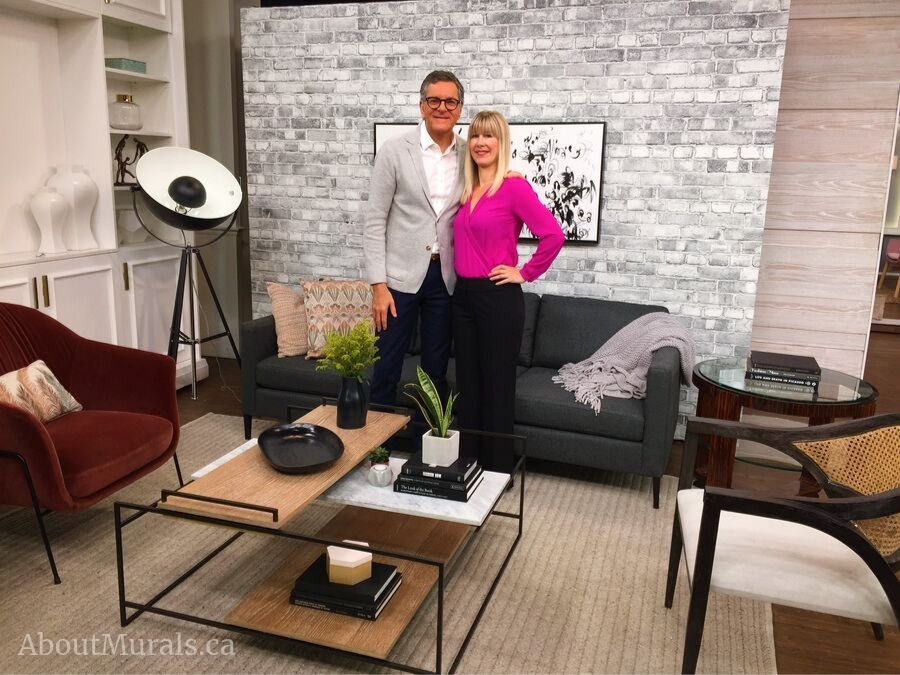 Adrienne stands with Brian Gluckstein in front of a grey brick wallpaper on set at Cityline