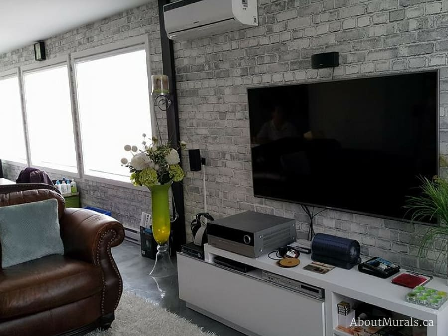 A grey brick wallpaper in a living room, sold by AboutMurals.ca