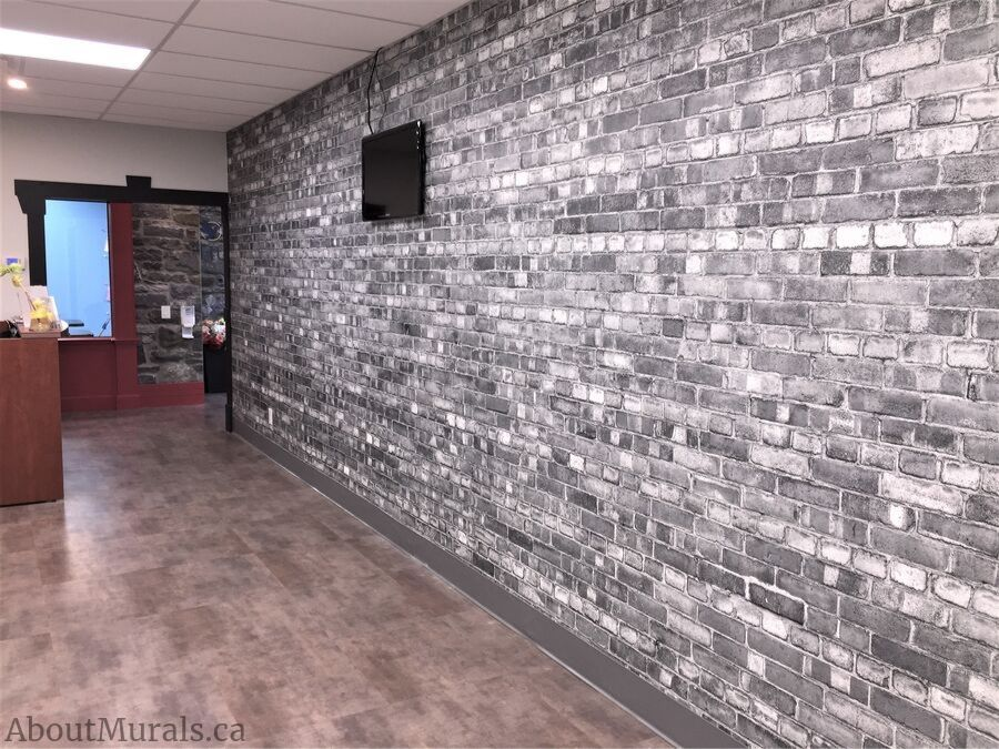 A grey brick wallpaper decorated the reception wall at the Pearl Hummingbird play center in Hamilton