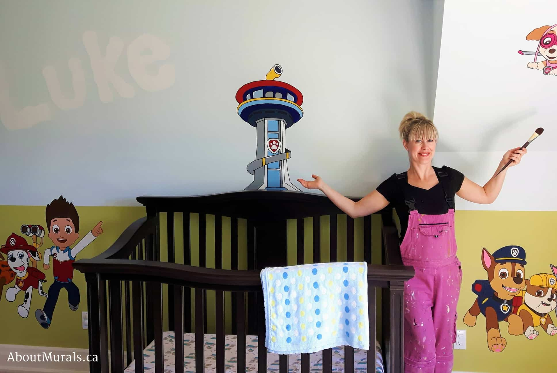 Mural painter Adrienne Scanlan stands next to the Paw Patrol mural she painted