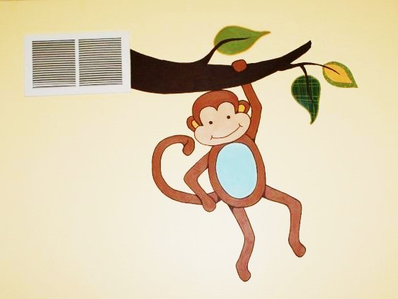A rainforest mural featuring a monkey hanging from a branch, painted by Adrienne of AboutMurals.ca