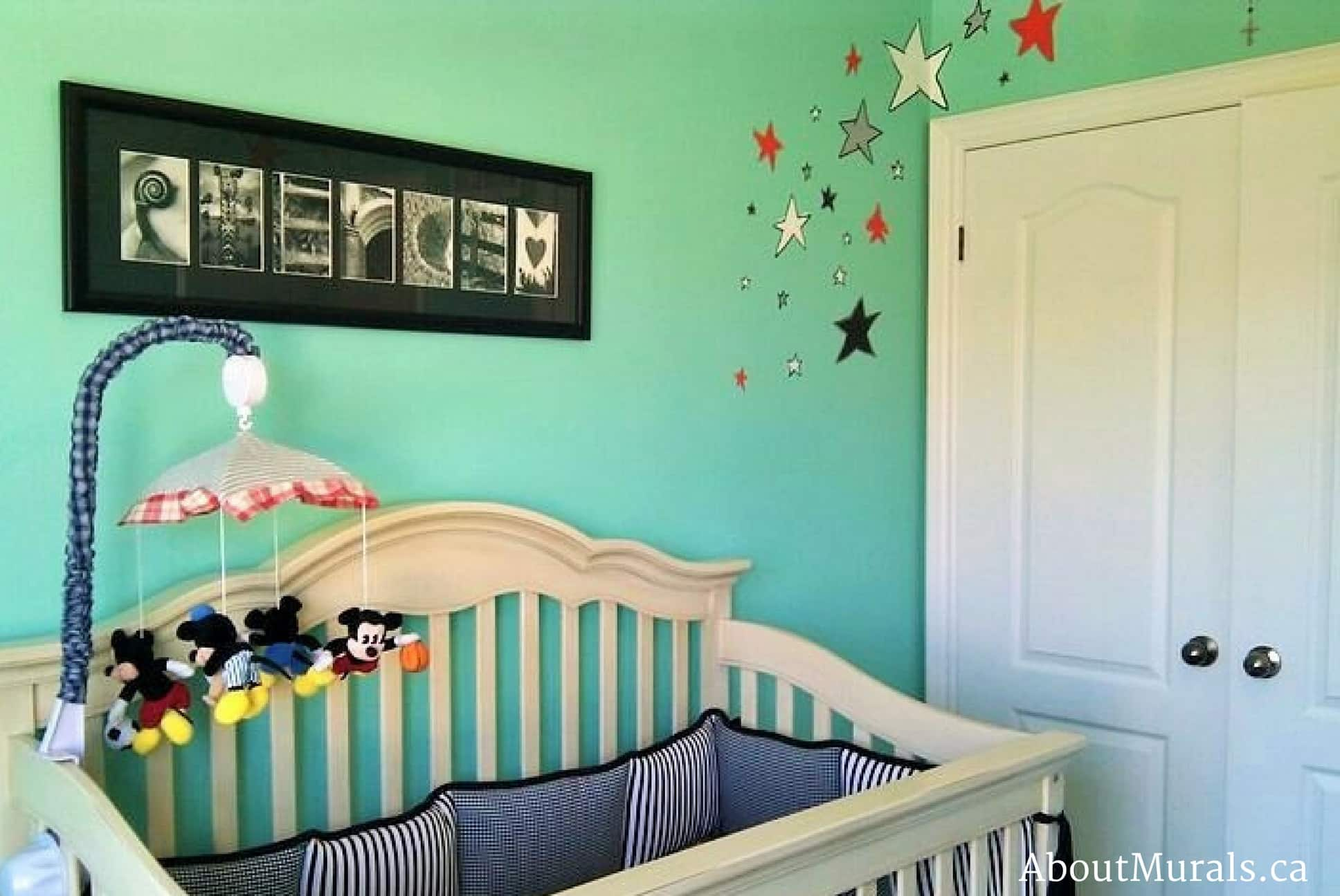 A kids wall mural featuring black, white, orange and silver stars scattered through a baby nursery