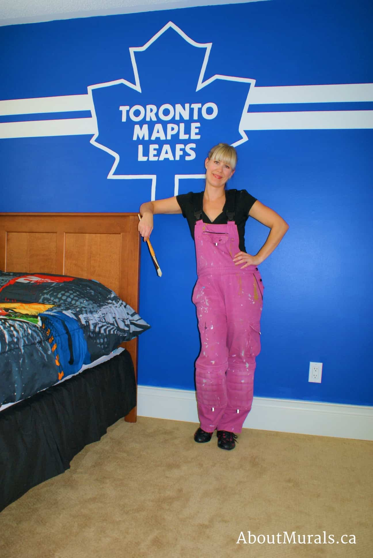 Mural painter Adrienne Scanlan stands next to a Toronto Maple Leafs logo she painted