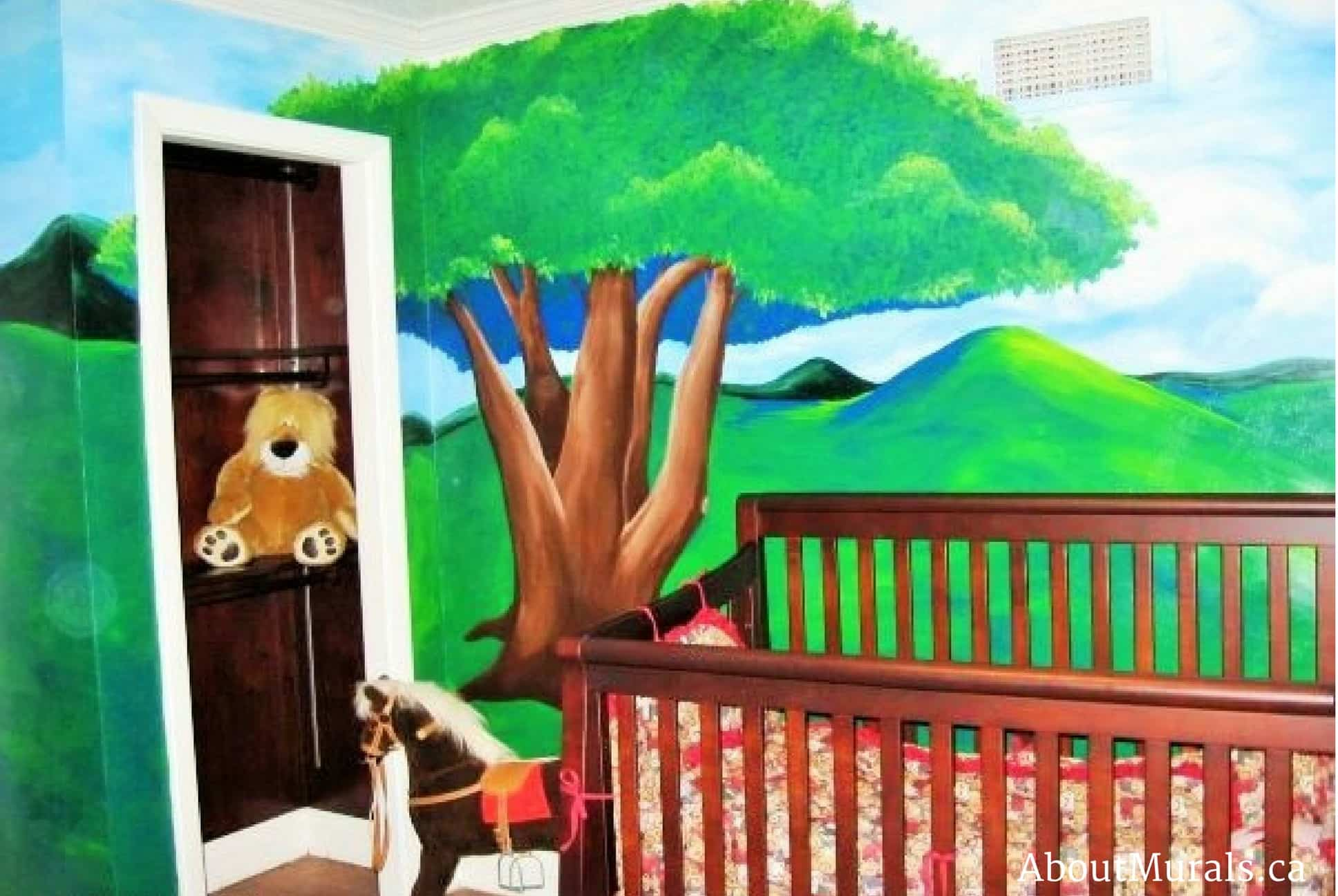 A kids wall mural featuring a tree over a baby crib
