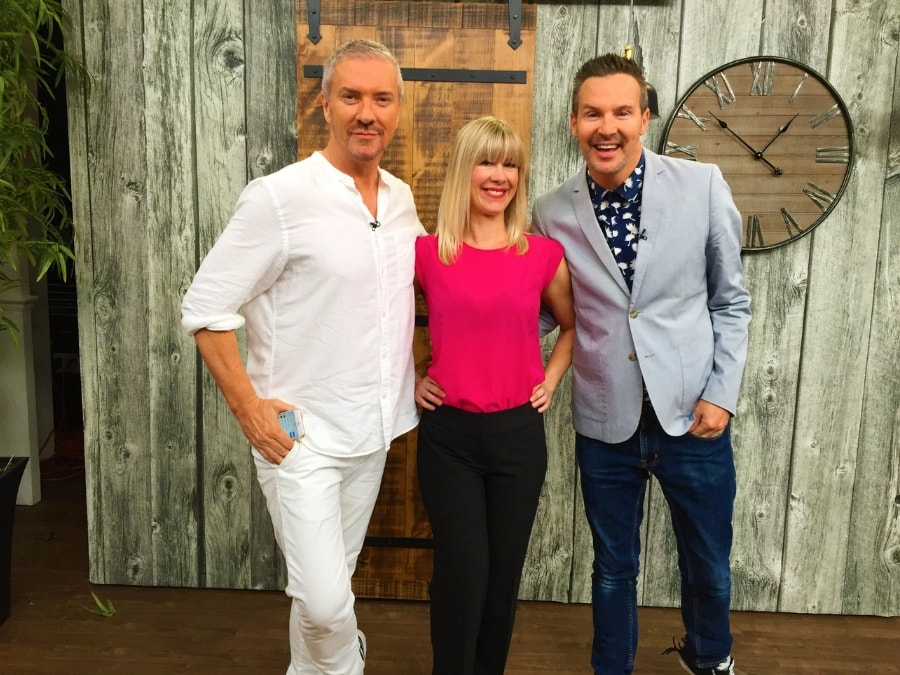 Adrienne stands with Colin and Justin on set at Cityline after she installed a wood wallpaper for their episode