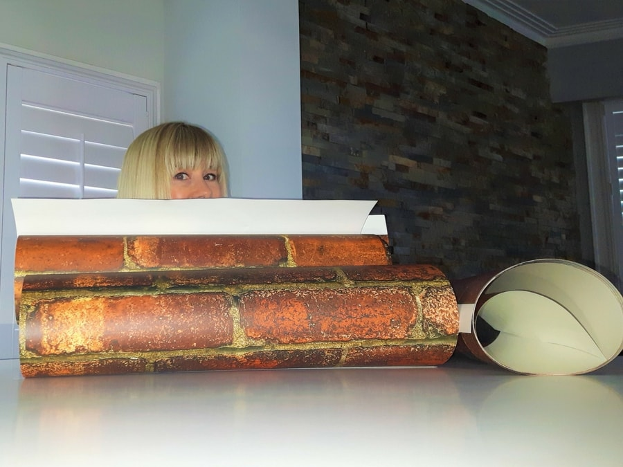 Adrienne Scanlan peeks out over a roll of faux brick wallpaper