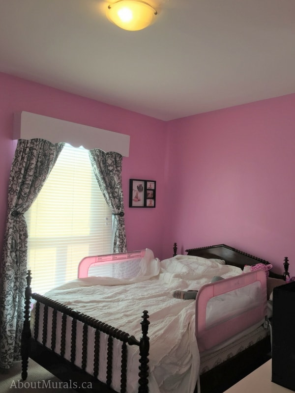 A pink bedroom with butterfly curtains before a kids mural is painted by Adrienne of AboutMurals.ca