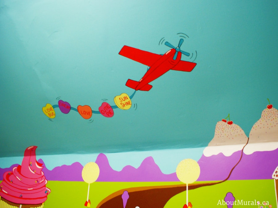 A candy mural featuring an airplane totting sweet tart candy in the sky, painted by Adrienne of AboutMurals.ca