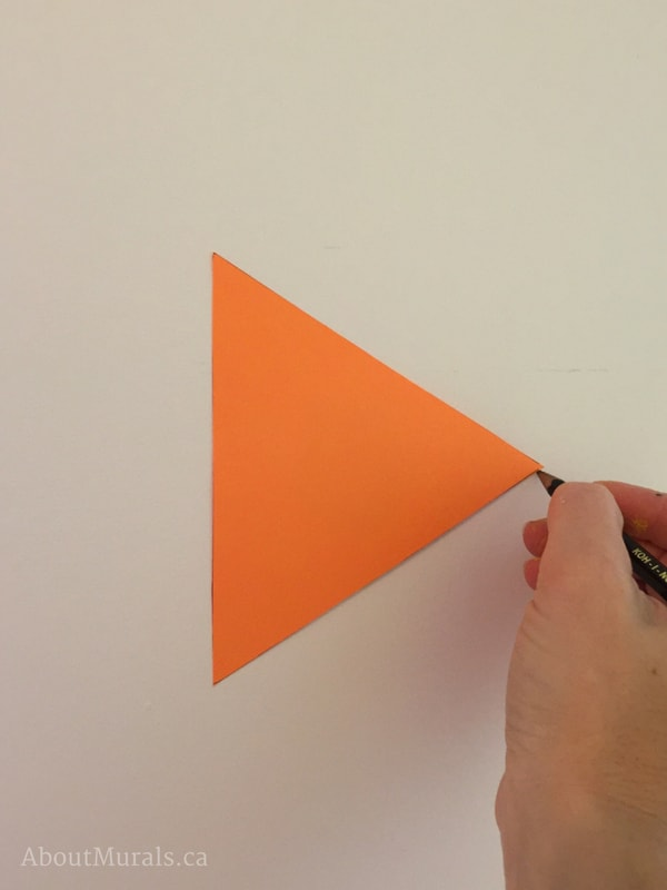 An orange triangle stencil used by muralist Adrienne of AboutMurals.ca