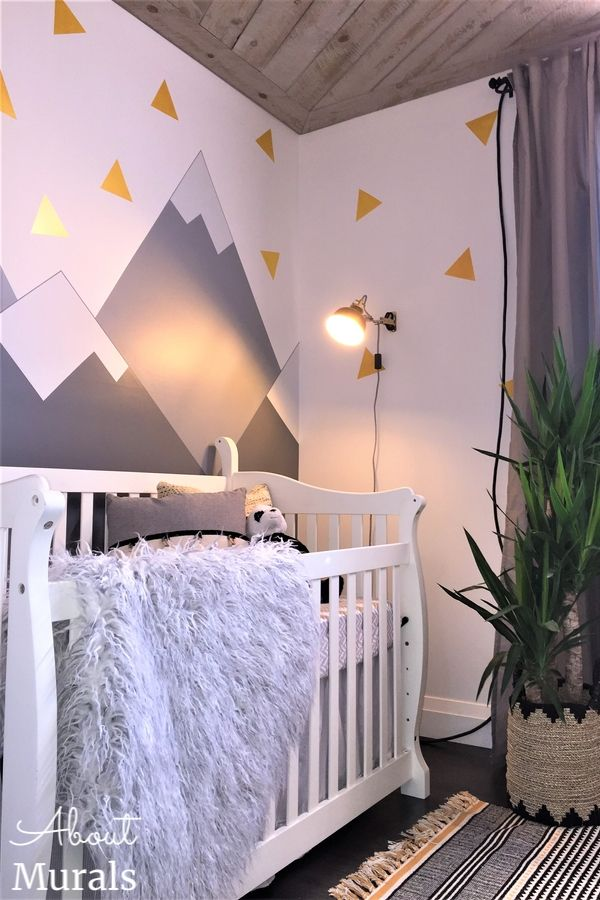 The corner of a baby's nursery with a mountain mural in the background