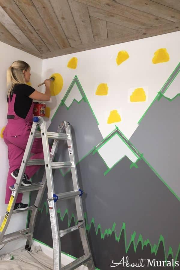 Muralist Adrienne paints triangles in a DIY Mountain Mural.