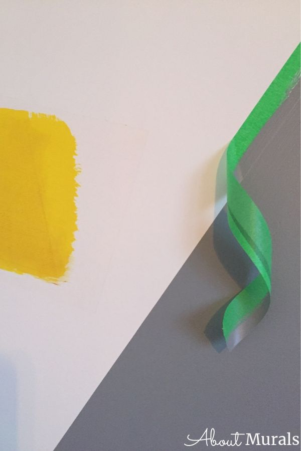 Green painters tape is peeled off a grey mountain mural