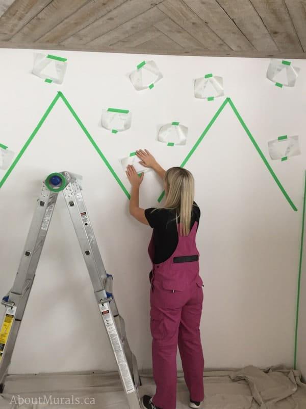 Muralist Adrienne Scanlan tapes off a DIY Mountain Mural