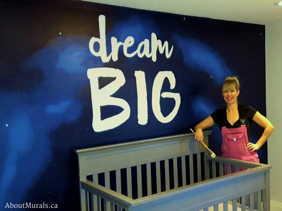 Muralist Adrienne of AboutMurals.ca stands next to the Dream Big mural she painted