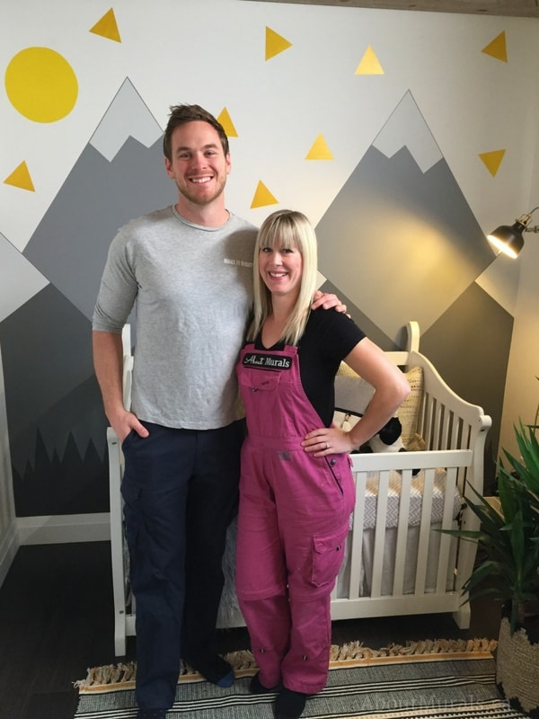 Holmes Next Generation star Mike Holmes Jr stands with muralist Adrienne in front of the mountain mural featured on the television show