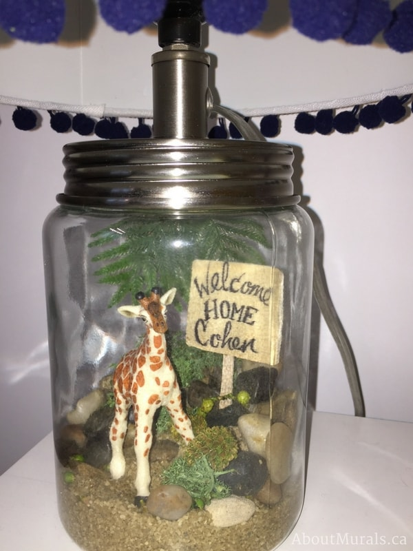 """A close up of a personalized lamp with a giraffe, rocks, leaves and sign reading """"Welcome Home Cohen"""" created by Sherry Holmes for the Holmes Next Generation TV Show."""