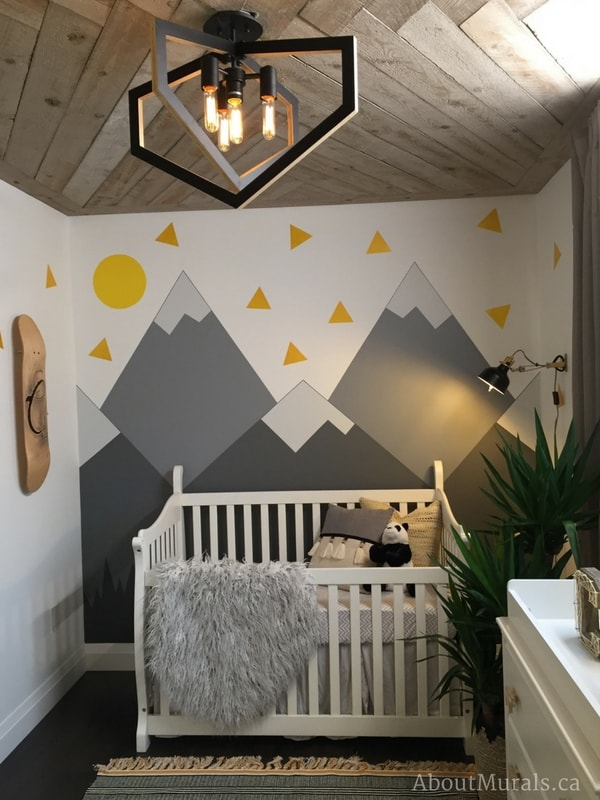 A mountain mural painted by Adrienne of AboutMurals.ca for the Holmes: Next Generation TV show sits under a rustic wooden ceiling built by Mike Holmes Junior.