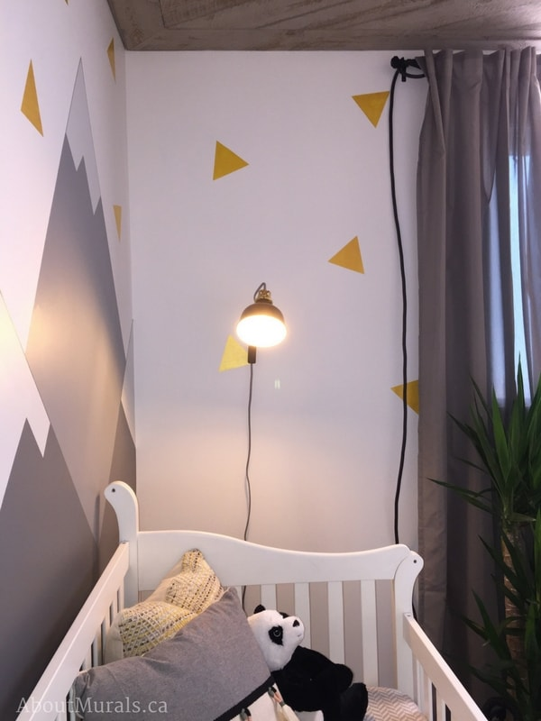 Triangles painted next to a mountain mural by Adrienne of AboutMurals.ca decorate a wall over a baby's crib.