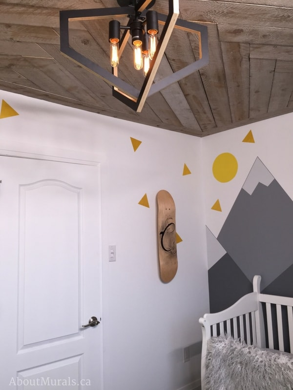 """A mountain mural, painted by Adrienne of AboutMurals.ca, sits beside a rustic, custom skateboard with the initial """"C"""" for baby Cohen."""