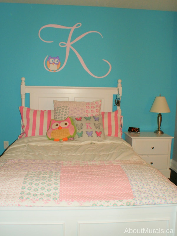 An owl mural painted with a letter K on turquoise walls by Adrienne of AboutMurals.ca