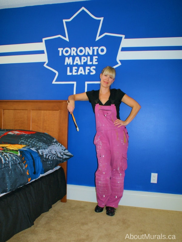 Muralist, Adrienne of AboutMurals,ca, stands next to a Toronto Maple Leafs mural she painted