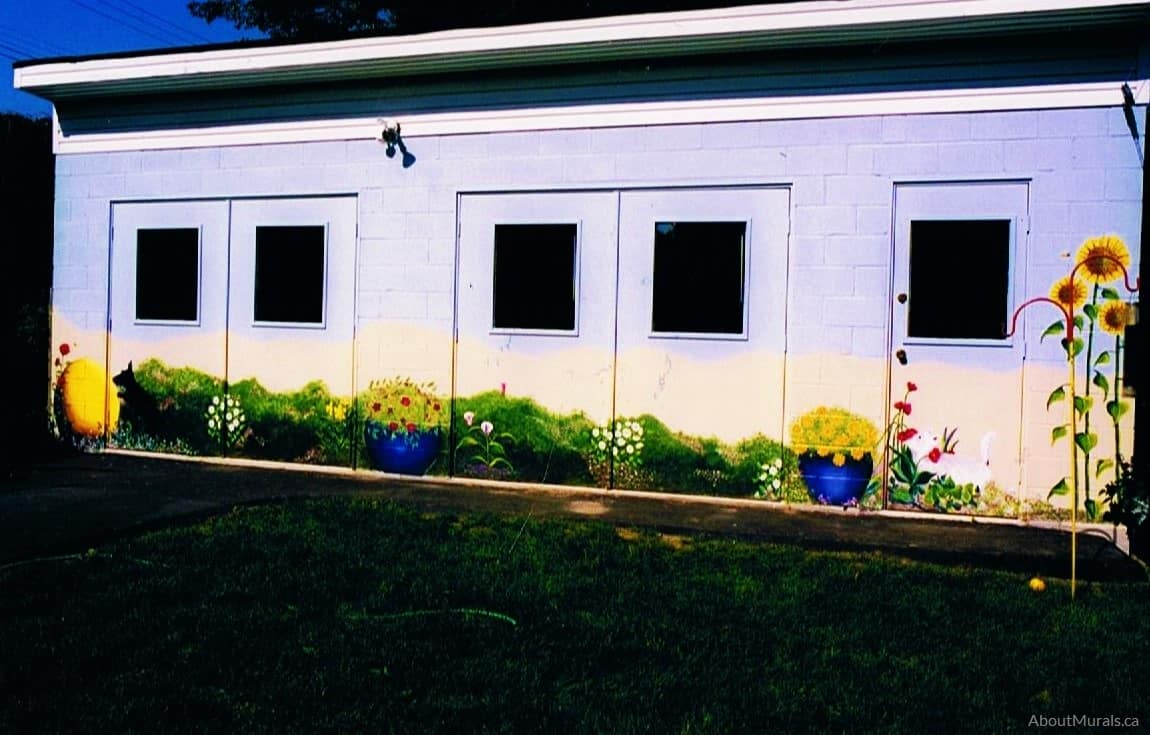 A garden mural featuring flowers and dogs painted by Adrienne of AboutMurals.ca