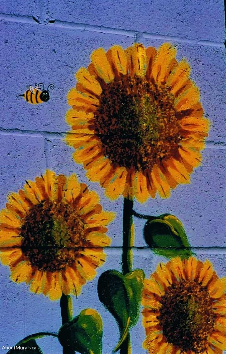 Sunflowers and a bee are painted in a garden mural by Adrienne of AboutMurals.ca