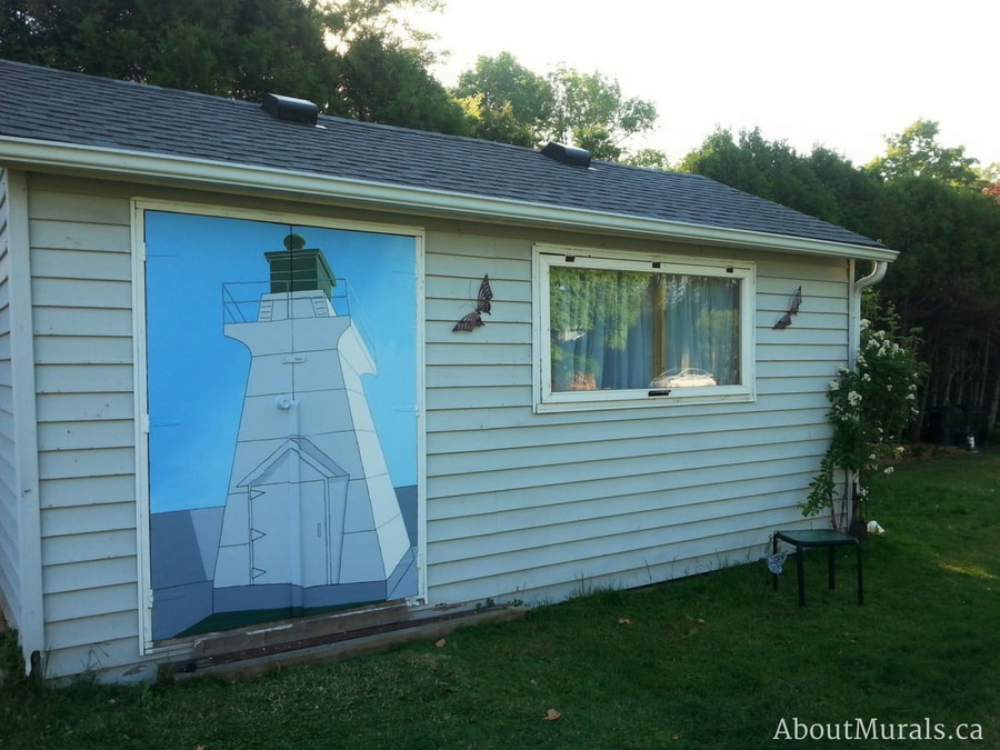 A lighthouse mural painted on a shed by Adrienne of AboutMurals.ca