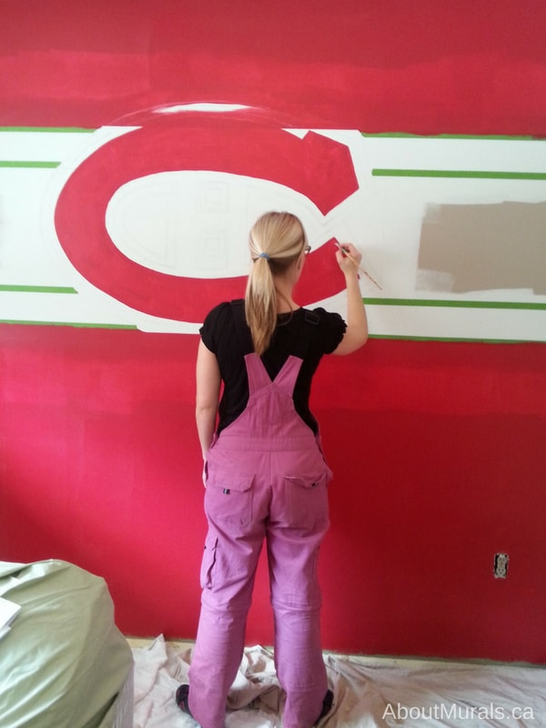 Muralist Adrienne of AboutMurals.ca paints a Montreal Canadiens wall