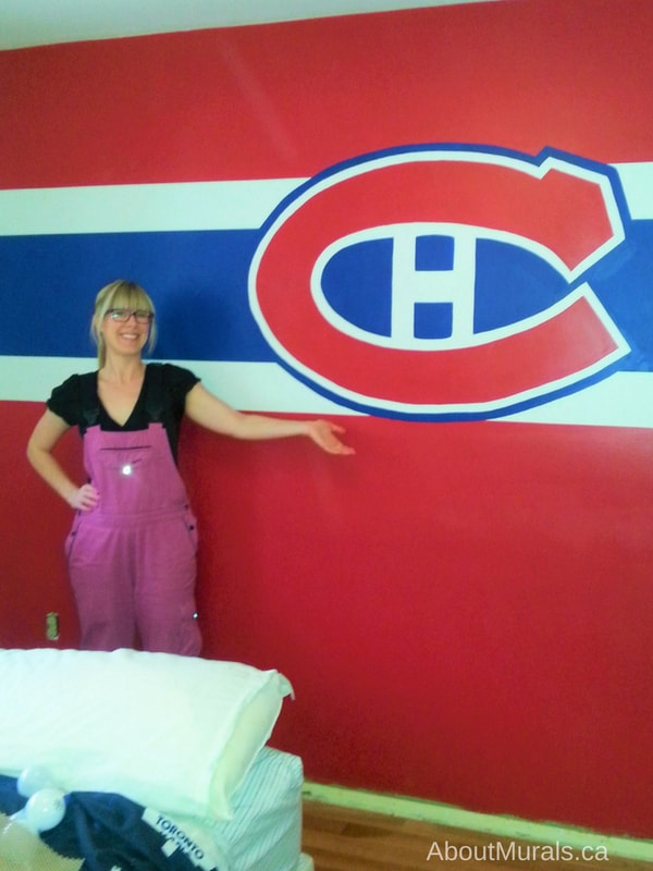 Muralist Adrienne of AboutMurals.ca stands next to the Montreal Canadiens wall she painted