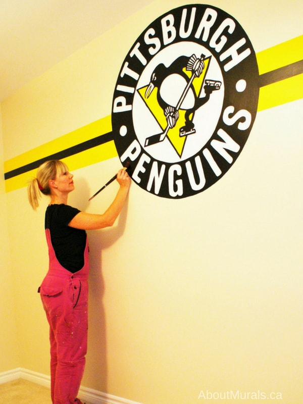 Muralist Adrienne of AboutMurals.ca paints a Pittsburgh Penguins mural