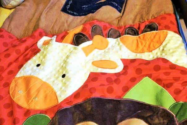 The bedding used as inspiration for the giraffe in a safari mural painted by Adrienne of AboutMurals.ca
