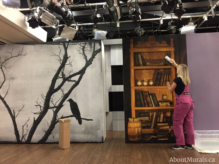 Adrienne of AboutMurals.ca hangs two Halloween wall murals on set at Cityline