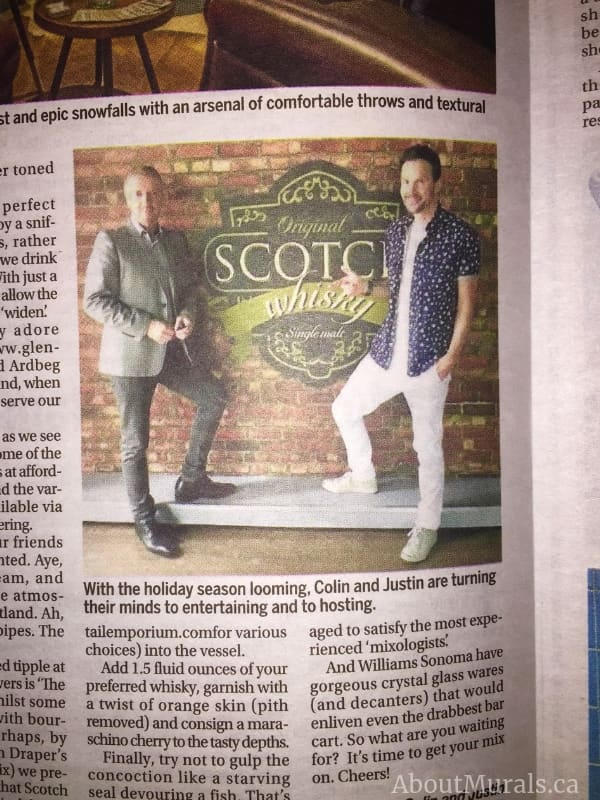 Colin and Justin standing in front of a custom wallpaper, created by AboutMurals.ca, in a Toronto Sun newspaper article