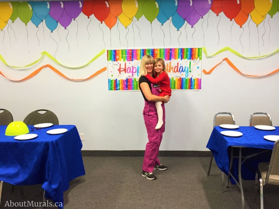 Adrienne Scanlan and her daughter stand under a balloon mural she painted in Hamilton, Ontario.