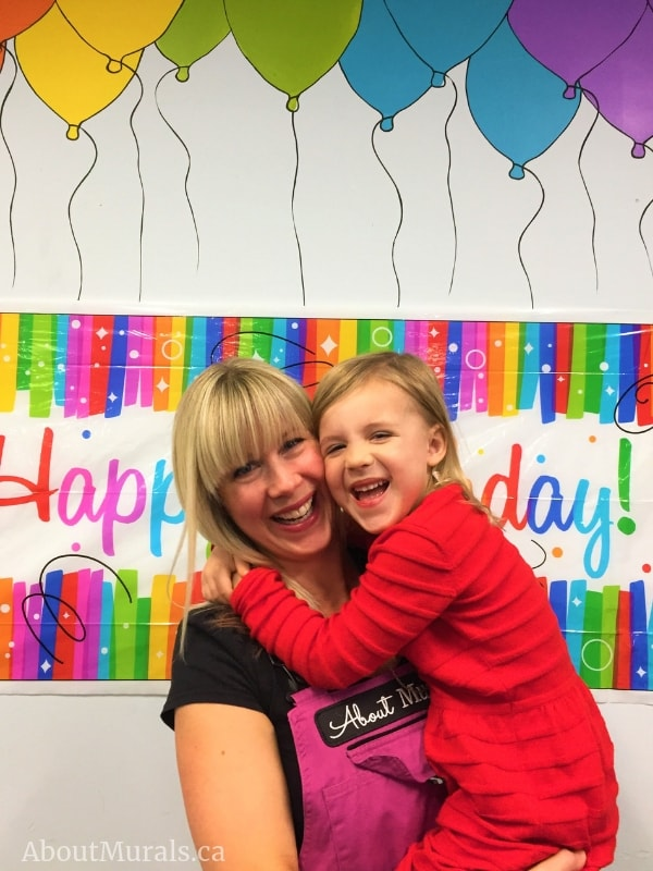 Muralist Adrienne of AboutMurals.ca hugs her daughter under balloons she painted on a wall