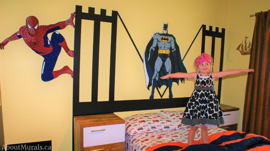 A girl jumps on a bed under a Batman Wall Mural painted by Adrienne of AboutMurals.ca