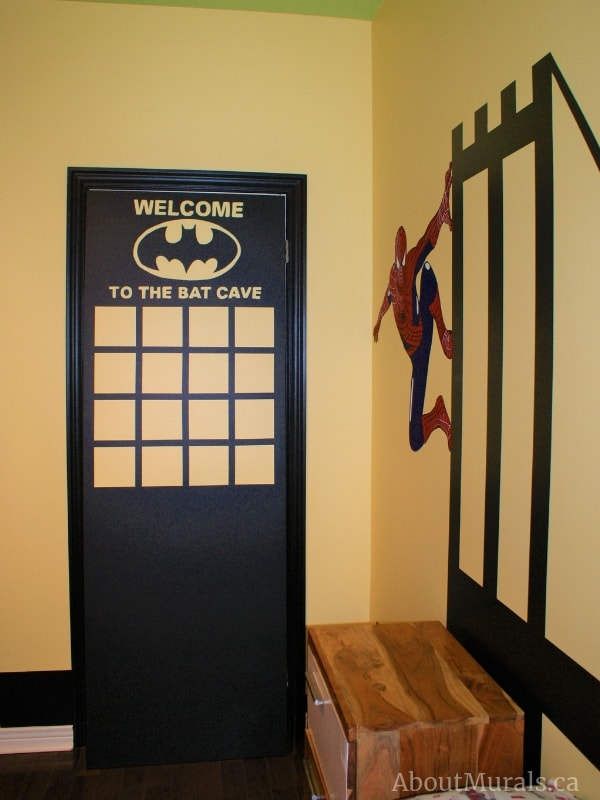 """Adrienne of AboutMurals.ca painted a closet door into a skyscraper with the words, """"Welcome to the batcave"""""""