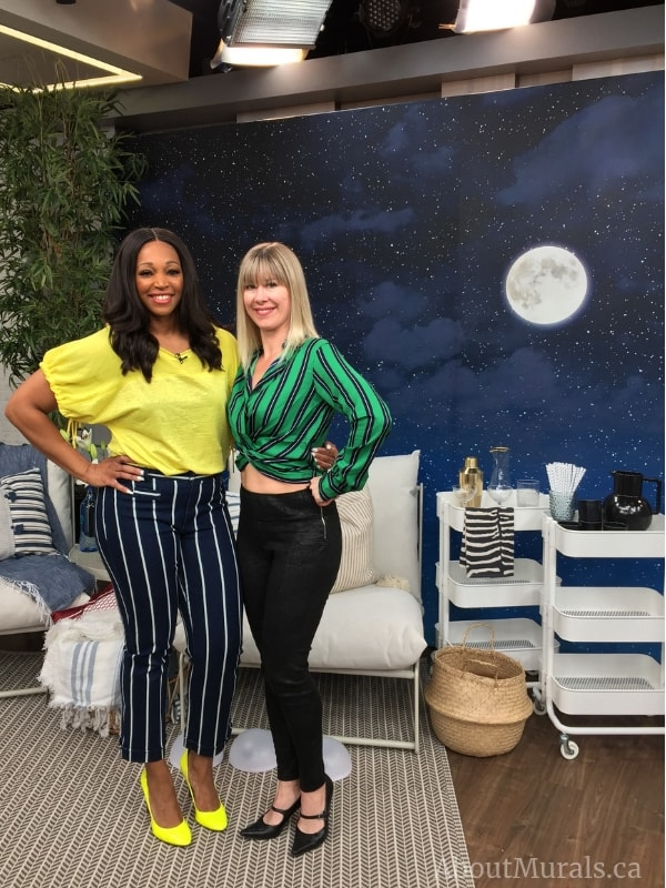 Adrienne and Tracy Moore stand in front of a starry moonlit sky wallpaper on set at Cityline.