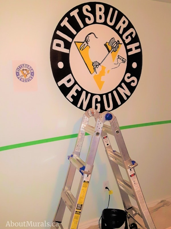A Pittsburgh Penguins mural in the process of being painted by Adrienne of AboutMurals.ca