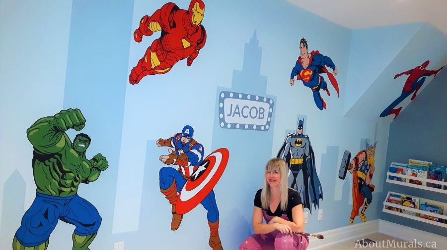 Muralist Adrienne of AboutMurals.ca crouches under the superhero mural she painted in Carlisle, Ontairo