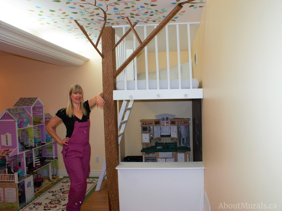 Adrienne of AboutMurals.ca stands next to an indoor treehouse she painted