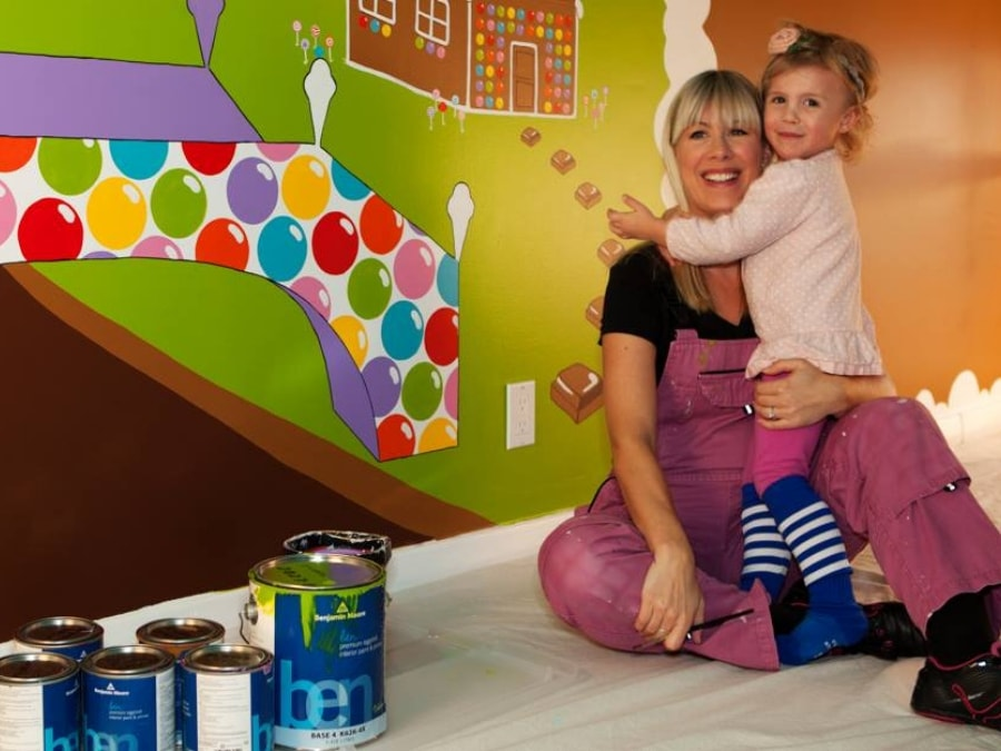 Adrienne of AboutMurals.ca sits with her daughter Audrey in front of a candy world mural